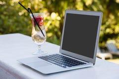 La opinión de alto ángulo del ordenador portátil y el cóctel beben en el restaurante fotografía de archivo libre de regalías