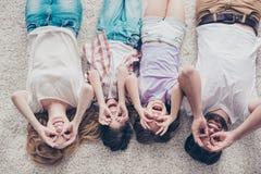 La opinión de alto ángulo de la familia de cuatro miembros feliz es el bromear, mintiendo en fotografía de archivo libre de regalías