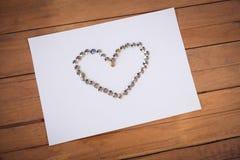 La opinión de alto ángulo de los pernos de papel arregló en forma del corazón en el papel Fotografía de archivo libre de regalías