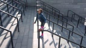La opinión de alto ángulo la muchacha atlética activa que hace calentamiento de la pierna ejercita en las escaleras en el estadio almacen de metraje de vídeo