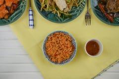 La opinión de arriba de la endecha plana de una tabla puso con los platos chinos de la carne del arroz Foto de archivo