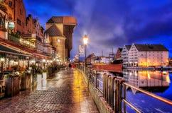 La opinión de la noche de la grúa medieval del puerto llamó Zuraw en el río de Motlawa en Gdansk, Polonia Fotografía de archivo libre de regalías