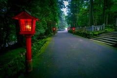La opinión de la noche del acercamiento a la capilla de Hakone en un bosque del cedro con muchos linterna roja encendida para arr fotos de archivo