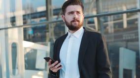 La opinión de la rotación un hombre barbudo que hace una pausa el terminal de aeropuerto, aplicaciones su teléfono, saca las gafa almacen de metraje de vídeo