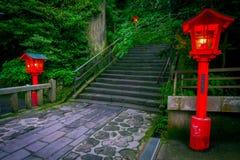 La opinión de la noche del acercamiento a la capilla de Hakone en un bosque del cedro con muchos linterna roja encendida para arr fotografía de archivo