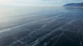 La opinión de perspectiva aérea del hielo azul profundo hermoso texturizó la superficie congelada del lago Baikal desde arriba metrajes
