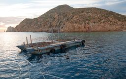La opinión de la salida del sol de Fishermans del barco de la fuente del cebo en las tierras termina en Cabo San Lucas en Baja Ca imagen de archivo libre de regalías