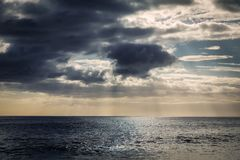La opinión de la tarde con el throug brillante del sol se nubla en la playa de Makua, Oahu fotografía de archivo