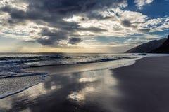 La opinión de la tarde con el throug brillante del sol se nubla en la playa de Makua, Oahu foto de archivo libre de regalías