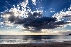 La opinión de la tarde con el throug brillante del sol se nubla en la playa de Makua, Oahu fotos de archivo