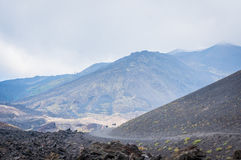 La opinión de Volcano Etna con los turistas y la lava empiedra todos alrededor en la niebla Imagen de archivo libre de regalías