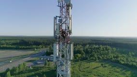 La opinión del abejón el hombre del técnico del sistema de la antena de la telecomunicación se vistió en el uniforme y el casco q