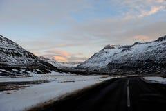 La opinión del camino como la montaña curvy de la nieve en el fondo, Islandia foto de archivo