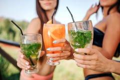 La opinión del corte de tres soportes de los modelos y sostiene tres vidrios con los cócteles Hay una bebidas coloreadas anaranja foto de archivo