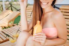 La opinión del corte la muchacha se sienta en sunbed y sonríe Ella sostiene la botella anaranjada en mano izquierda La muchacha e imagen de archivo libre de regalías