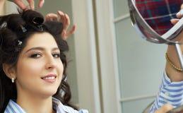 La opinión del primer de la mano y el peine de un peluquero que peina un nuevo peinado en un cliente dirigen en salón de pelo foto de archivo