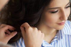 La opinión del primer de la mano y el peine de un peluquero que peina un nuevo peinado en un cliente dirigen en salón de pelo imagenes de archivo