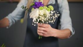 La opinión del primer de manos del artista floral de sexo femenino profesional que prepara un ramo, flor de corte del florista pr metrajes