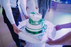 La opinión del primer del pastel de bodas blanco adornado con las cintas verdes Foto de archivo libre de regalías