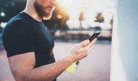 La opinión del primer el atleta hermoso muscular que comprueba deporte resulta en el uso del smartphone y el reloj elegante despu Fotos de archivo