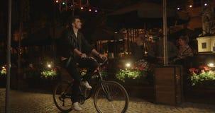 La opinión del primer el hombre joven que monta la bici a lo largo de los cafés preciosos del vintage en la noche almacen de metraje de vídeo