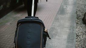 La opinión del primer la mujer joven con la maleta que camina a través de la calle, llega a la nueva ciudad y a ir al hotel almacen de metraje de vídeo