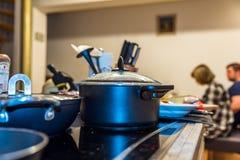 La opinión del primer misted encima de la tapa de la cacerola que cocinaba en la cocina eléctrica moderna sobre gente en la tabla Imagen de archivo
