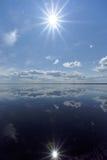 La opinión del río con las nubes reflejó en ella, el sol en el marco y la reflexión del sol, Volga, Rusia Foto de archivo