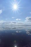 La opinión del río con las nubes reflejó en ella, el sol en el marco y la reflexión del sol, Volga, Rusia Fotos de archivo libres de regalías