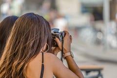 La opinión dos muchachas que se sientan en una terraza al aire libre, una de ellas toma la foto con la cámara imagenes de archivo