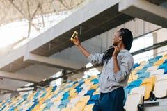 La opinión el adolescente afroamericano sonriente que toma el selfie en el fondo de los asientos en el estadio Fotos de archivo