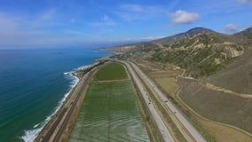 La opinión hermosa del paisaje del campo y de la carretera con los coches y de la costa de maíz del Océano Pacífico tiró desde ar almacen de metraje de vídeo
