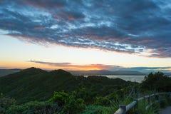 La opinión imponente de la puesta del sol sobre las colinas y el océano de los montains en Byron Bay, Australia Imagen de archivo libre de regalías