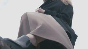 La opinión inferior una muchacha con el pelo largo en capa negra presenta para una foto metrajes