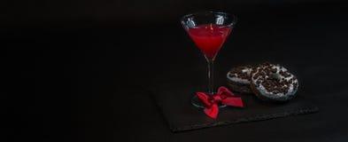 La opinión izquierda sobre una bebida cosmopolita un vidrio de martini adornó w Fotos de archivo