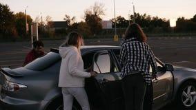 La opinión rara amigos jovenes de moda de un multirace los cuatro está corriendo por zona de aparcamiento de la alameda y se sien almacen de video