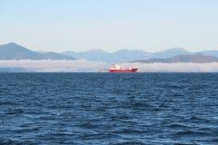 La opinión sobre buque de carga también llamó el carguero en las aguas de la bahía en la península de Kamchatka, Rusia de Avacha fotografía de archivo