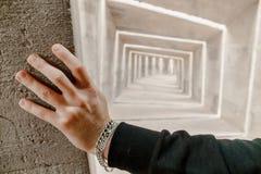 La opinión sobre caucásico sirve la mano con las pulseras toca la pared Colocación, ojeada y pensando él en futuro y la opción de imágenes de archivo libres de regalías