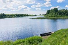 La opinión sobre el río con la isla y el barco de madera puso para arriba en riverbank Fotos de archivo libres de regalías