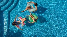 La opinión superior aérea la familia en piscina desde arriba, la madre y los niños nadan y se divierten en agua el vacaciones de  fotos de archivo libres de regalías