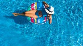La opinión superior aérea la muchacha hermosa en piscina desde arriba, relaja nadada en el buñuelo inflable del anillo en agua en Imagenes de archivo