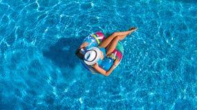La opinión superior aérea la muchacha hermosa en piscina desde arriba, relaja nadada en el buñuelo inflable del anillo en agua en Fotografía de archivo libre de regalías