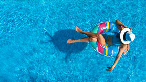 La opinión superior aérea la muchacha hermosa en piscina desde arriba, relaja nadada en el buñuelo inflable del anillo en agua en Imágenes de archivo libres de regalías