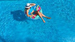 La opinión superior aérea la muchacha hermosa en piscina desde arriba, relaja nadada en el buñuelo inflable del anillo en agua en Imagen de archivo libre de regalías