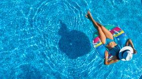 La opinión superior aérea la muchacha hermosa en piscina desde arriba, relaja nadada en el buñuelo inflable del anillo y se divie Fotografía de archivo libre de regalías