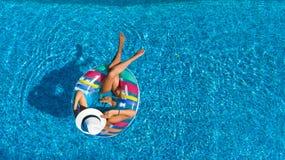 La opinión superior aérea la muchacha hermosa en piscina desde arriba, relaja nadada en el buñuelo inflable del anillo y se divie Foto de archivo libre de regalías
