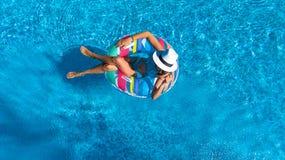 La opinión superior aérea la muchacha hermosa en piscina desde arriba, relaja nadada en el buñuelo inflable del anillo y se divie Foto de archivo