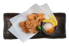 La opinión superior aislada el japonés frió el pollo Karaage con cocinar el papel servido con la salsa Tentsuyu del tempura Fotografía de archivo