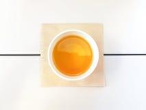La opinión superior de la forma del té de la mañana le gusta un huevo en la tabla blanca con el tejido de Brown Imagen de archivo libre de regalías
