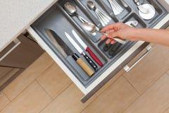 La opinión superior del alto ángulo cosechó la foto del cajón abierto de la cocina de la mano de la mujer por el tirador de puert fotos de archivo